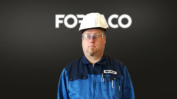 Picture of Marko Manninen, a Foreman at Fortaco Kalajoki Factory with Fortaco Logo in the background